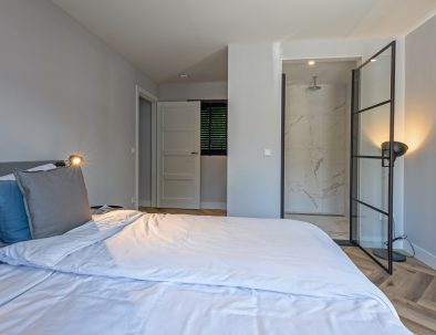 Master bedroom with ensuite bathroom in holiday home Island of Texel